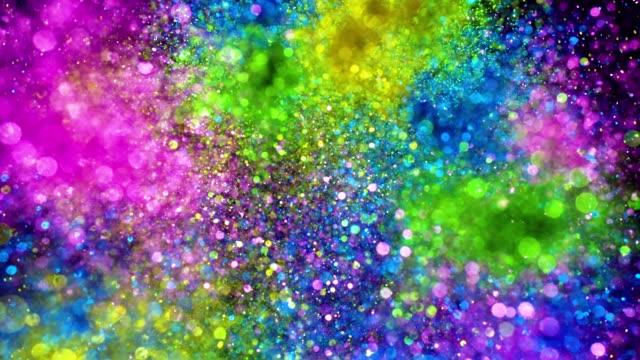 vídeos de stock e filmes b-roll de multi colored glitter exploding towards camera and becoming defocused, shining bokeh on black background - carnaval evento de celebração