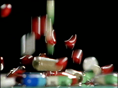 multi colored pills cascade onto surface of counter - prescription medicine stock videos & royalty-free footage