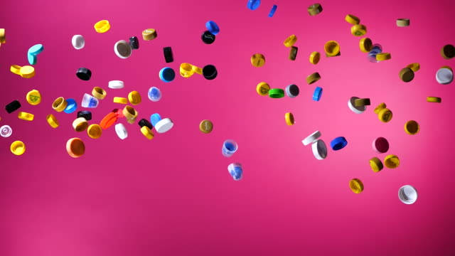 multi colored plastic bottle caps and falling down on pink background - cap stock videos & royalty-free footage