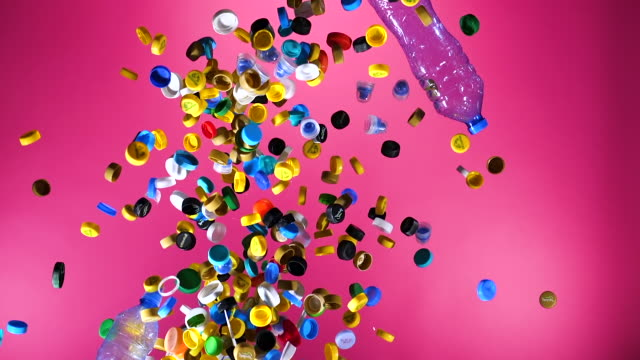 multi colored plastic bottle caps and plastic bottles falling down on pink background - reusable stock videos & royalty-free footage
