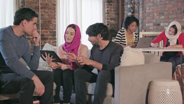 vídeos y material grabado en eventos de stock de profesionales multi étnico interactúan con tableta digital - pañuelo de cabeza