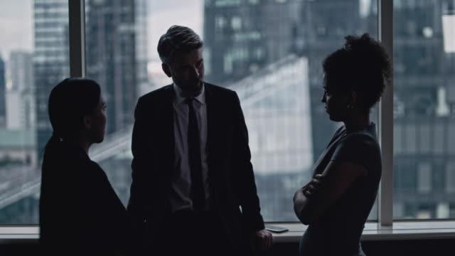 vídeos de stock, filmes e b-roll de equipe de negócios multiétnica falando. panorama da cidade em segundo plano - vestuário de trabalho formal