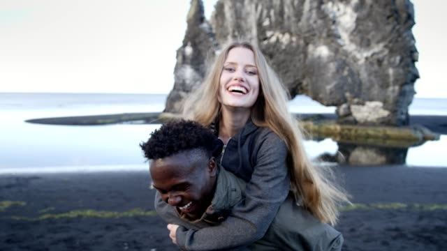 Multi ethnic couple having fun on the black beach