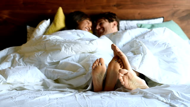 Multi Ethnic Couple in Bed Being Playful