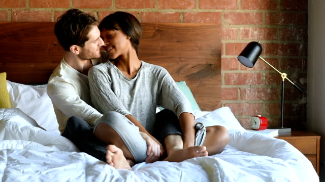 multi ethnic couple in bed hugging - legs crossed at ankle stock videos and b-roll footage