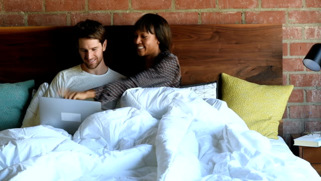 multi ethnic couple in bed watching movie on their laptop - bed stock videos & royalty-free footage