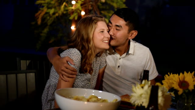 Multi Ethnic Couple Kiss at a Summer BBQ