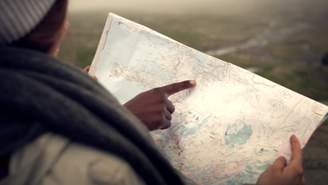 multi ethnic couple planning trip with a map and compass - journey stock videos & royalty-free footage