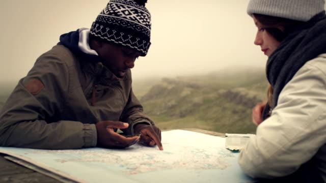vidéos et rushes de multi ethnique couple planification voyage avec une carte et une boussole - détermination