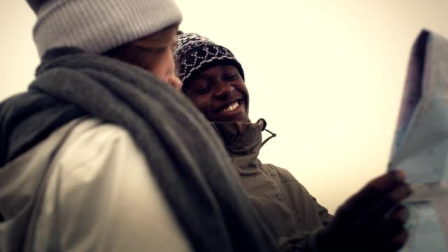 multi etniska par planerar resa med karta och kompass - bergskedja bildbanksvideor och videomaterial från bakom kulisserna