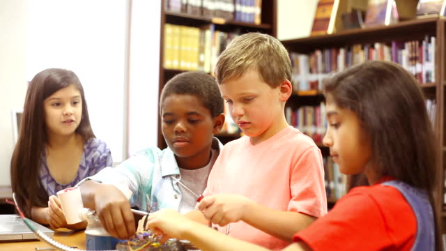 Multi ethnic elementary age students build robot in science class.
