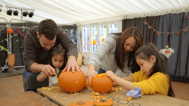 multi ethnic family carving pumpkins - carving craft product stock videos & royalty-free footage
