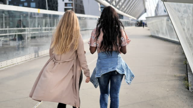 multi ethnic female friends walking in nordic city - youth culture stock videos & royalty-free footage