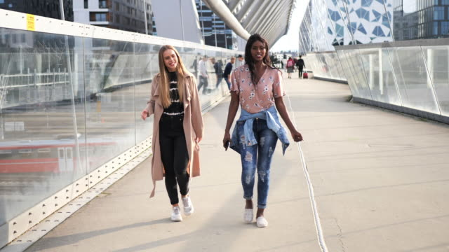 multi ethnic female friends with perfect smiles walking in the city - customs stock videos & royalty-free footage