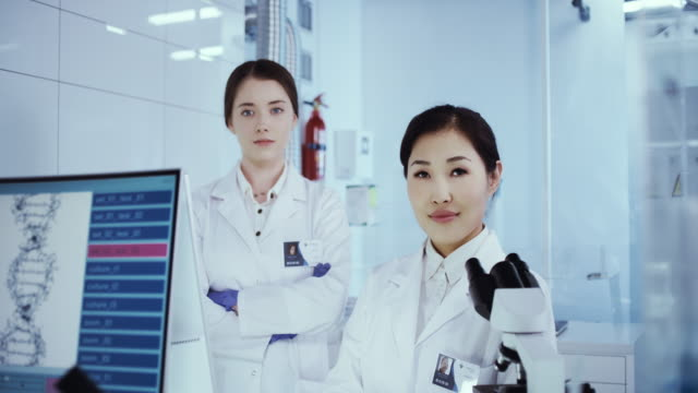 multi ethnic female scientists satisfied with her work. futuristic genetic research laboratory - pride stock videos & royalty-free footage
