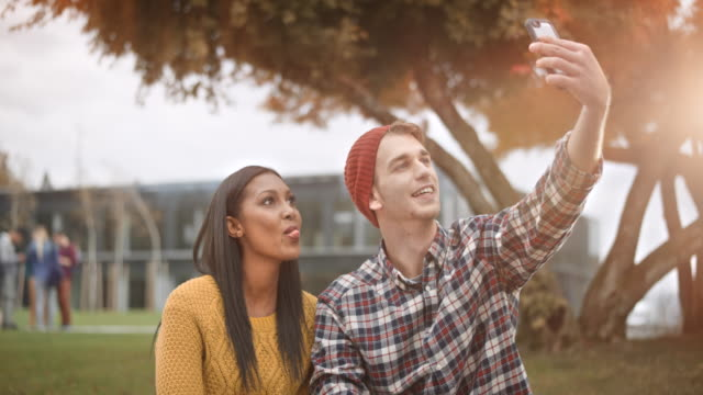 Multi ethnic female student and her Caucasian friend taking a selfie in the park