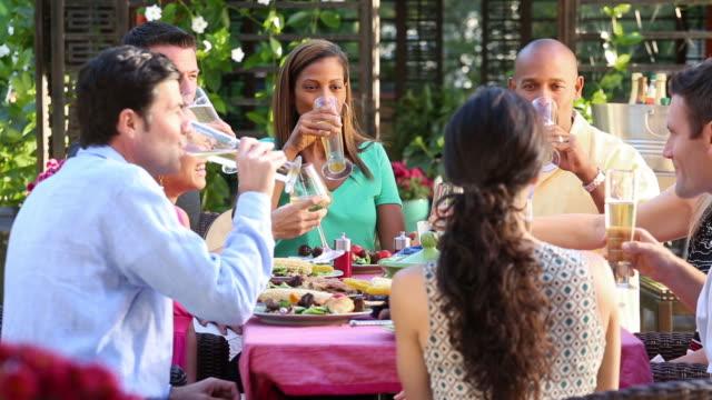 Multi ethnic friends at backyard barbecue.