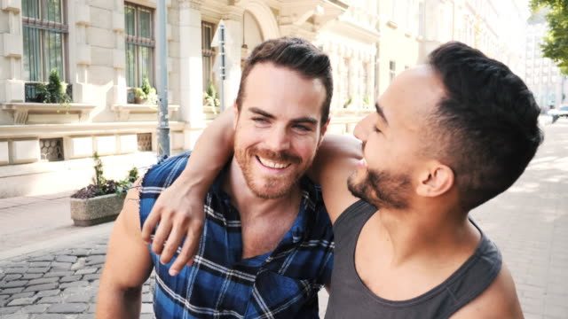 multi ethnic gay couple sharing romance in summer in the city - image stock videos & royalty-free footage