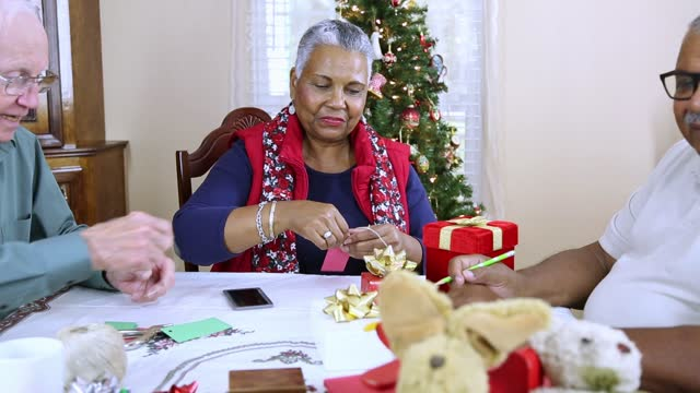 stockvideo's en b-roll-footage met multi etnische groep van actieve senioren ontmoeten om cadeaus voor kinderen in de buurt wrap. - cadeau