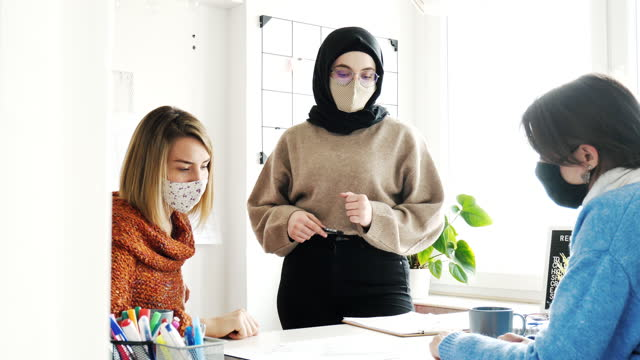 multi ethnic group of creative employees working in office after reopening, wearing face mask to prevent covid-19 spreading in office - computer equipment stock videos & royalty-free footage