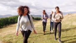 A multi ethnic group of five happy young adult friends walking across a field during a mountain hike, close up