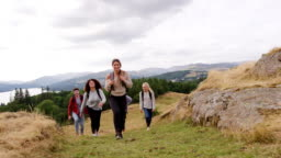 A multi ethnic group of five young adult friends smile while hiking across a field to the summit during a mountain hike, close up