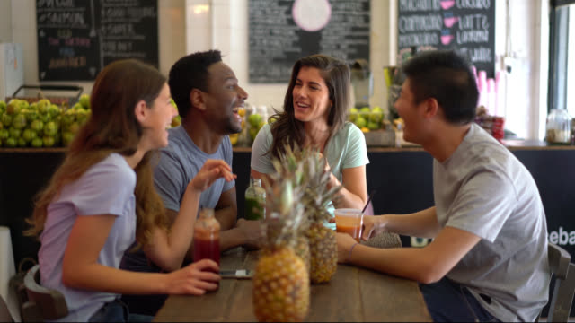 Multi ethnic group of friends at a juice bar having fun talking and laughing while enjoying a juice