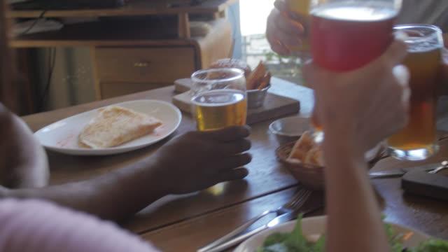 Multi-ethnische Gruppe von Freunden in einem Pub trinken Bier und Essen Hamburger
