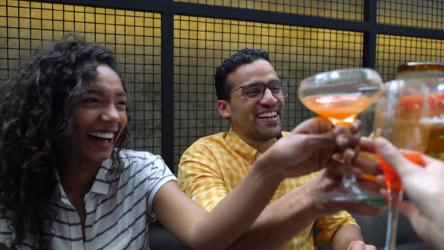 multi ethnic group of friends having drinks at a bar making a toast - cocktail stock videos & royalty-free footage