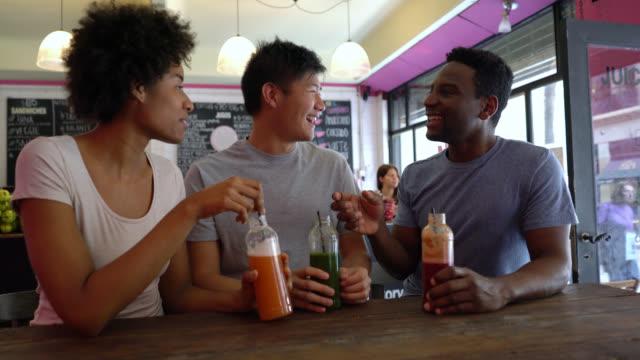 vidéos et rushes de multi ethnique groupe d'amis s'amuser dans un bar à jus et faire un toast avec leurs jus en bouteille - voix