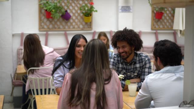 vidéos et rushes de groupe multi ethnique d'amis ayant l'amusement parlant et souriant au restaurant en attendant l'ordre - multi ethnic group