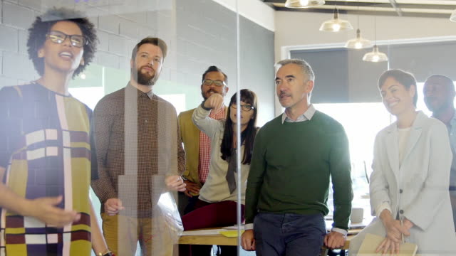 Multi ethnic group of office workers in meeting studying graph on glass partition