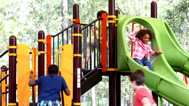 multi ethnic group of school children playing on school playground. - parco giochi video stock e b–roll