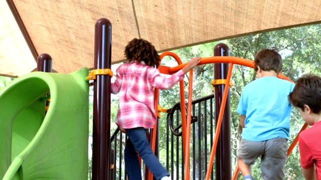 vídeos y material grabado en eventos de stock de multi étnico grupo de niños jugando en el patio de la escuela. - estructura metálica para niños