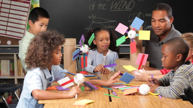 CU Multi Ethnic Group of School Children Using Model Windmill to Lift Bucket / Richmond, Virgnia, USA