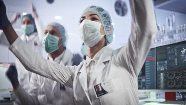 multiethnisches laborteam feiert durchbruch in der biogefährlichen forschung - joy stock-videos und b-roll-filmmaterial