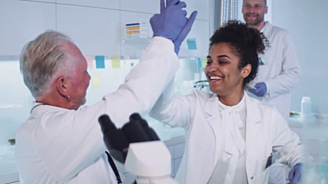 multi ethnic laboratory team celebrating breakthrough in research. high five - success stock videos & royalty-free footage