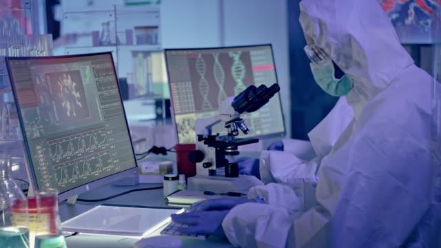 vídeos de stock e filmes b-roll de covid-19 - multi ethnic laboratory team working on coronavirus. wearing protective suits - mutação genética