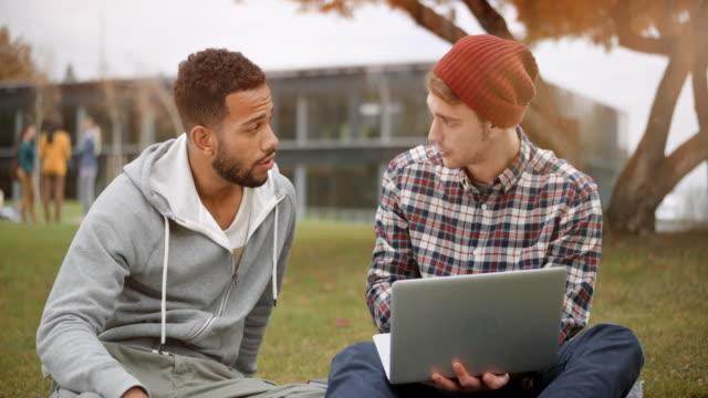vidéos et rushes de multi ethnique élève de sexe masculin et son ami caucasien masculin assis dans le parc et vérifier quelque chose sur le portable - campus
