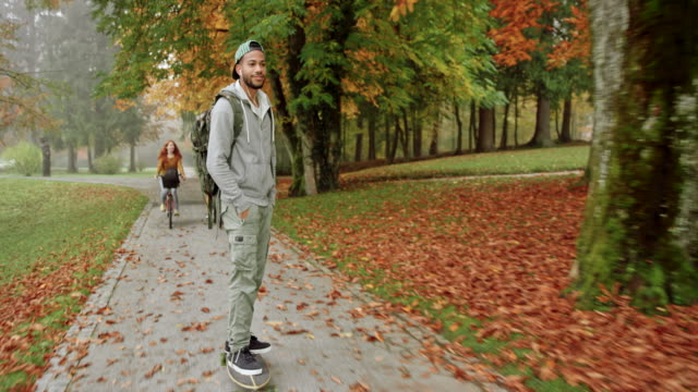 multi ethnic male student riding a longboard in a park on a foggy fall morning - university stock videos and b-roll footage