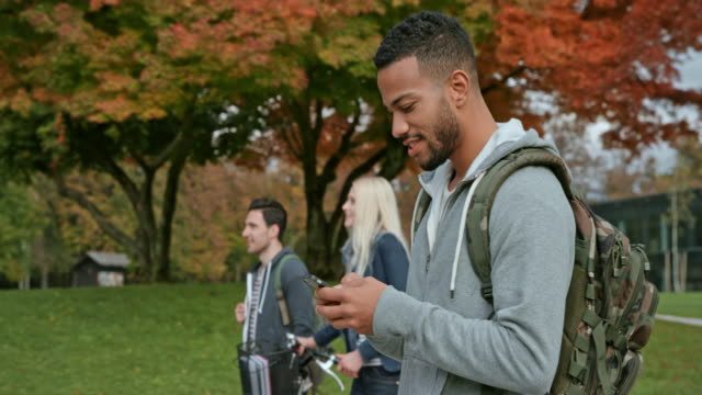 vídeos de stock e filmes b-roll de ts multi ethnic male student texting while walking through a park - mochila saco
