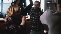 Multi ethnic millennials dance crazy at a party. Slow motion Students get wild and silly at holiday celebration. Emotion