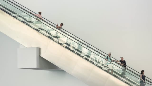 Multi ethnic People using an escalator in a modern shopping mall, isolated against a white background