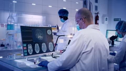 vídeos y material grabado en eventos de stock de equipo de investigación multiétnico que estudia el escaneo de ondas cerebrales - científica