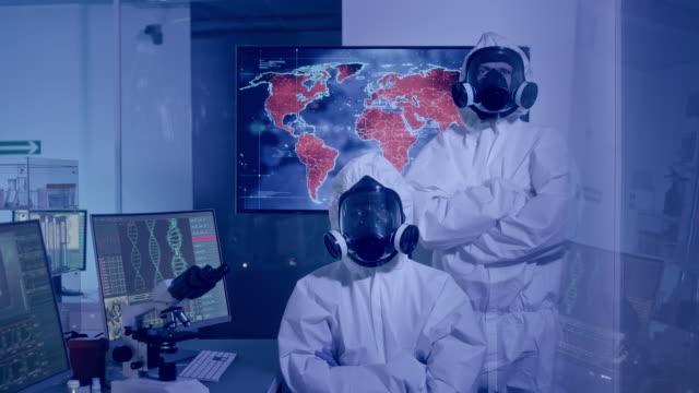 多民族科学者は仕事に満足した。世界の病原体の伝染を研究する - クリーンスーツ点の映像素材/bロール