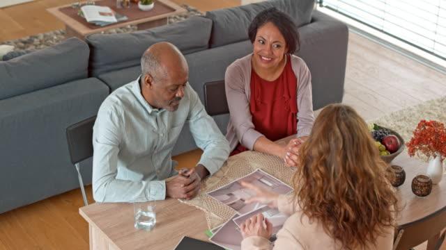 Multi ethnic senior couple consulting their interior designer at home