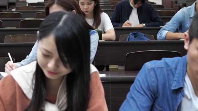 講義室で試験を行う多民族学生 - オンライン講義後に大学に戻る - 試験点の映像素材/bロール