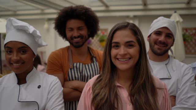 vídeos de stock e filmes b-roll de multi ethnic team and business owner of a restaurant all facing camera smiling with arms crossed - empregada de mesa