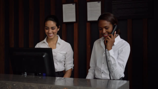 vídeos de stock e filmes b-roll de multi ethnic team of receptionist working at the front desk of hotel smiling - rececionista