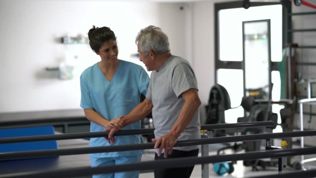 multi ethnic team of therapists at a physical recovery clinic helping patients do their therapy one with a senior man and at the background with a young man - physical therapy stock videos & royalty-free footage